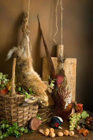 antique rifle: Autumn still life with hunting products, pheasant and hare Stock Photo