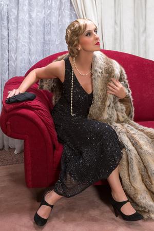 flapper: Charleston dama con un vestido flapper sentado en un sill�n de lujo