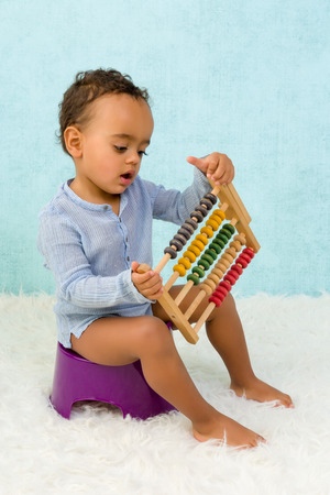 pissing: Potty training of a cute African toddler boy playing with an abacus