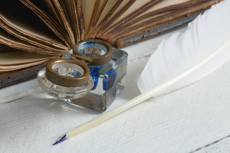 ink well: Feather quill, blue ink pot and medieval book on a rustic white painted table Stock Photo