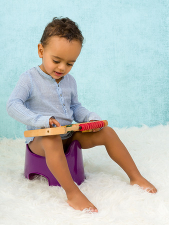potty training: Potty training of a cute African toddler boy playing with an abacus