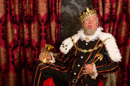borracho: Antiguo rey divertido emborracharse sosteniendo una copa de oro Foto de archivo