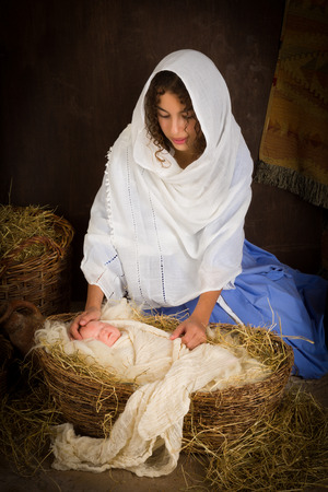virgin girl: Teenager girl playing the role of the Virgin Mary with a doll in a live Christmas nativity scene