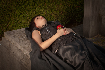 grieve: Dead gothic young woman lying on a tombstone