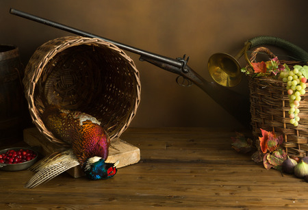 hunting rifle: Hunting still life with pheasant, basket and fruit