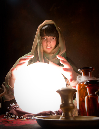 scrying: Beautiful gypsy reading the future in a crystral ball Stock Photo