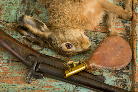 antique rifle: Old hunting scene with dead hare, rifle and leather gunpowder pouch