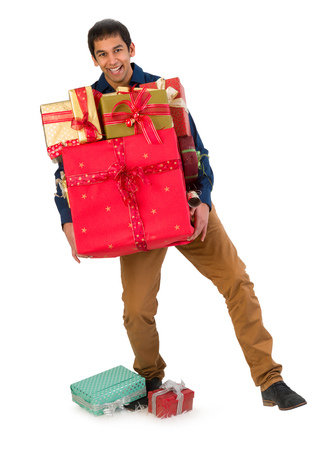 man carrying box: Happy young man holding too many Christmas presents Stock Photo