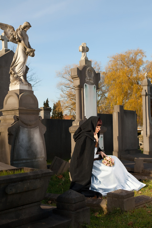 Victorian girl sitting on a grave and holding roses photo