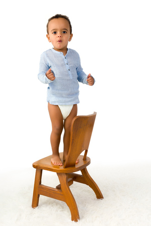18 month old: Cheerful little 18 month old toddler boy standing on a small wooden chair
