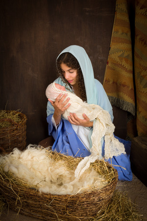 pesebre: Chica adolescente jugando el papel de la Virgen María con una muñeca en una escena viva de la natividad de Navidad