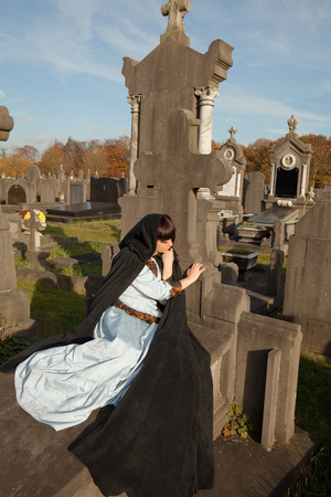 Young woman lying on a tombstone in a victorian dress photo
