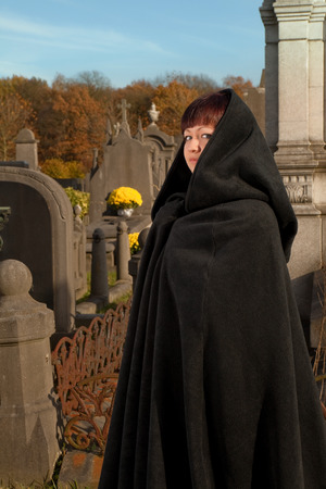 Woman with victorian cape visiting a very old graveyard photo