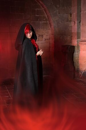 Foggy scene with a beautiful vampire gothic woman in a medieval abbey photo