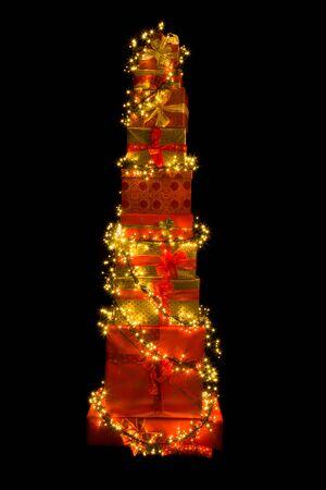 present: Stack of many christmas presents illuminated like a christmas tree Stock Photo