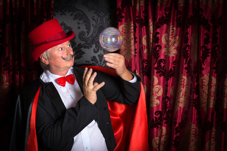 globe theatre: Senior magician performing on stage with a crystal ball