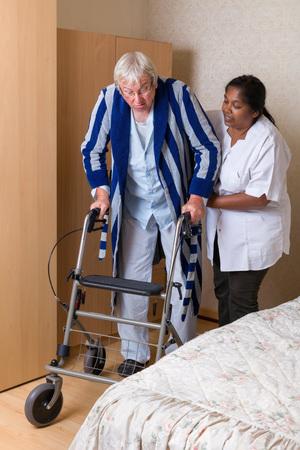 persona de la tercera edad: Abuelo mayores en hogares de ancianos utilizando un andador en su pijama