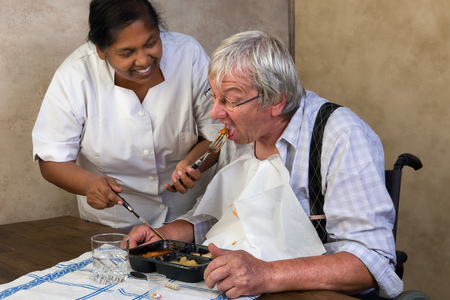 Nurse in old peoples home trying to make a patient eat his dinner