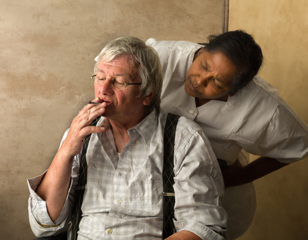 elderly: Elderly man in nursing home gets caught while smoking a cigarette Stock Photo