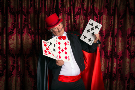 magic trick: Mature magician on stage performing a magic trick with cards