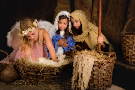 saint joseph: Little 7 year old angel visiting a nativity scene reenacted with a doll Stock Photo