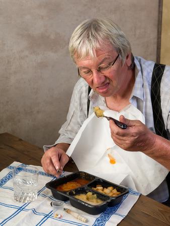 grumpy old man: Elderly man in nursing home disliking his ready made dinner Stock Photo