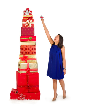 huge: Young woman putting one little gift on top of a huge stack of christmas presents
