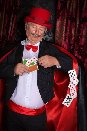 double chin: Mature magician on stage performing a magic trick with cards