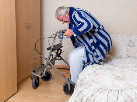 in pajama: Elderly grandfather in nursing home using a rollator in his pajama