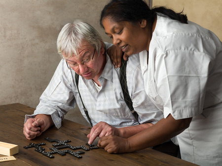 pensioner: Old pensioner in nursing home playing domino