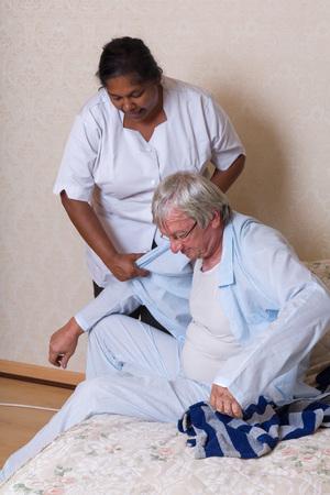 patient care: Nurse in nursing home helping elderly man getting dressed
