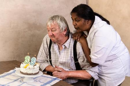 gateau anniversaire: Un homme âgé dans la maison de soins infirmiers soufflant des bougies sur son gâteau d'anniversaire Banque d'images