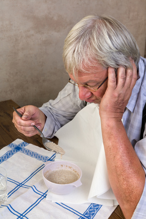 old people eating: Lonely elderly man disliking his porridge breakfast in the morning Stock Photo