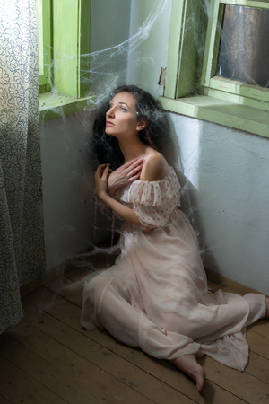 trapped: Young scared woman trapped in a corner with cobwebs or spiderwebs Stock Photo