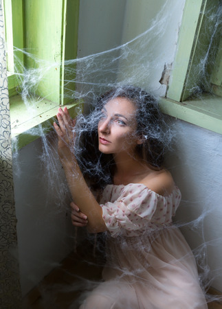 abandoned room: Young scared woman trapped in a corner with cobwebs or spiderwebs Stock Photo