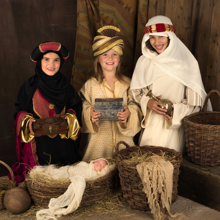 wisemen: Three girls playing as wisemen with a doll in a christmas nativity scene