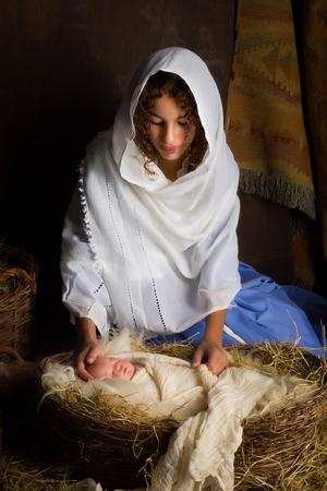nacimiento: Chica adolescente jugando el papel de la Virgen María con una muñeca en una escena viva de la natividad de Navidad