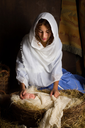 Tiener meisje speelt de rol van de Maagd Maria met een pop in een live Kerstmis Kerststal Stockfoto