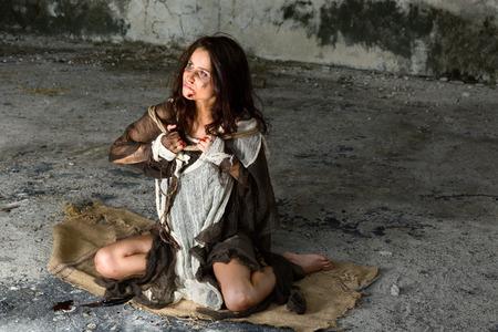 violencia: Mujer maltratada y asustado joven sentado en el piso de un edificio abandonado