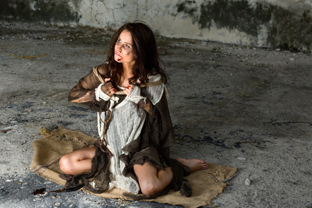 abused: Young abused and frightened woman sitting on the floor of a derelict building