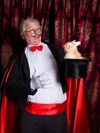 illusionist: Funny illusionist on stage with a rabbit in his top hat Stock Photo