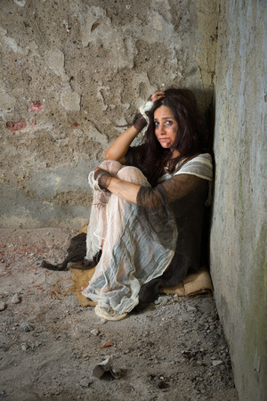 rape: Abused and frightened woman sitting in the corner of a derelict building