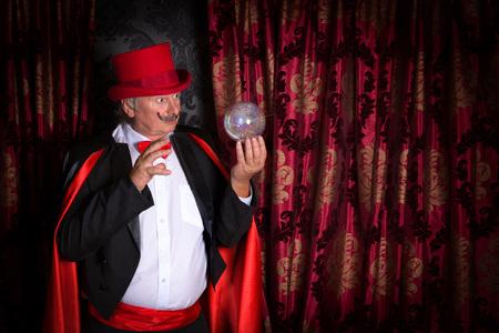 soothsayer: Mago Superior actuando en el escenario con una bola de cristal Foto de archivo
