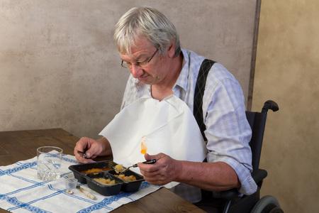 eating dinner: Elderly man in nursing home disliking his ready made dinner Stock Photo