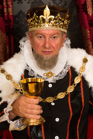 old vintage: Medieval king toasting with wine in a golden goblet Stock Photo