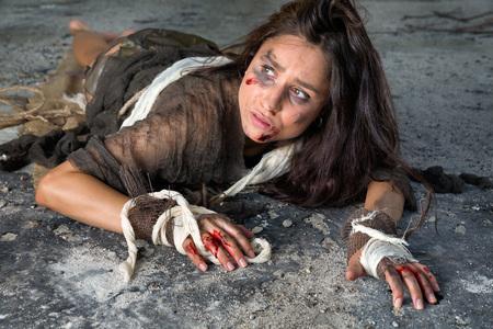 maltrato: Mujer maltratada y asustado joven sentado en el piso de un edificio abandonado