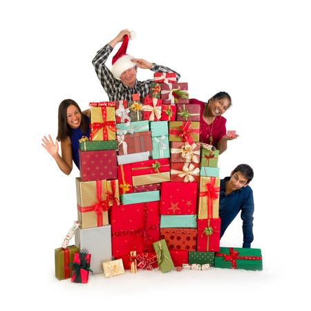 Mixed race family greeting you from behind a huge stack of christmas presents photo