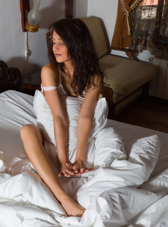 bedsheets: View on bedroom with a young woman sitting on her bed with a pillow
