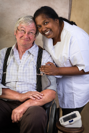enfermeria: Medir la presión arterial de un anciano en silla de ruedas Enfermera Foto de archivo