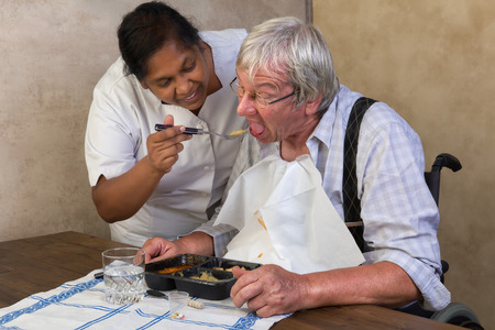 peoples: Nurse in old peoples home trying to make a patient eat his dinner